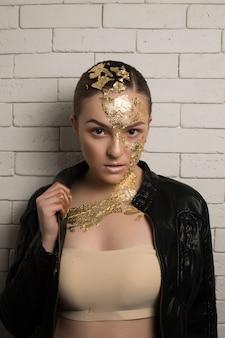 Gros plan d'une femme brune de luxe avec une feuille d'or sur le visage et le cou, portant une veste en cuir