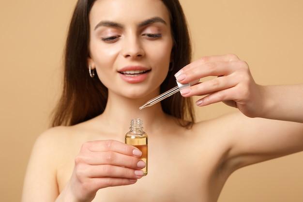 Gros plan femme brune à moitié nue avec une peau parfaite, maquillage nu, appliquer l'huile de la bouteille sur le visage isolé sur un mur pastel beige