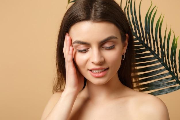 Gros plan sur une femme brune à moitié nue avec une peau parfaite, un maquillage nu et une feuille de palmier isolée sur un mur pastel beige