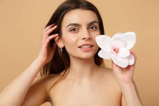 Gros plan femme brune à moitié nue avec une peau parfaite, maquillage nu isolé sur un mur pastel beige