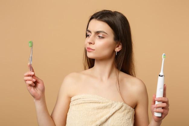Gros plan femme brune à moitié nue avec une peau parfaite maquillage nude tenir des pinceaux isolés sur un mur pastel beige