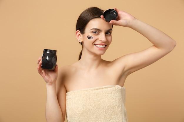 Gros plan sur une femme brune à moitié nue avec une peau parfaite, un masque noir de maquillage nu isolé sur un mur pastel beige