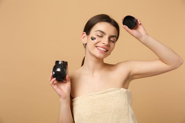 Gros Plan Sur Une Femme Brune à Moitié Nue Avec Une Peau Parfaite, Un Masque Noir De Maquillage Nu Isolé Sur Un Mur Pastel Beige Photo Premium