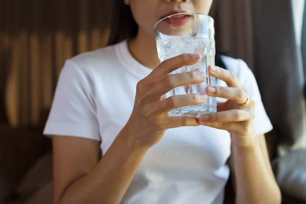 Gros plan d'une femme buvant dans un verre d'eau. concept de soins de santé