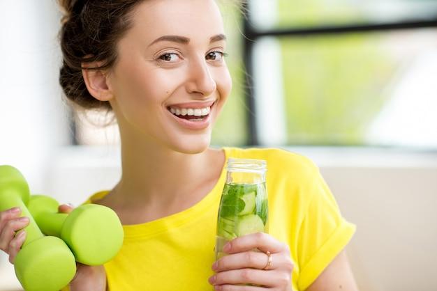 Gros plan d'une femme buvant de l'eau avec de la menthe, du concombre et du citron vert lors d'une séance d'entraînement avec des haltères. concept de régime de désintoxication