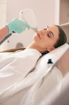 Gros plan d'une femme calme ayant les yeux fermés tout en étant dans un salon de beauté et ayant la procédure d'épilation au laser sur son visage