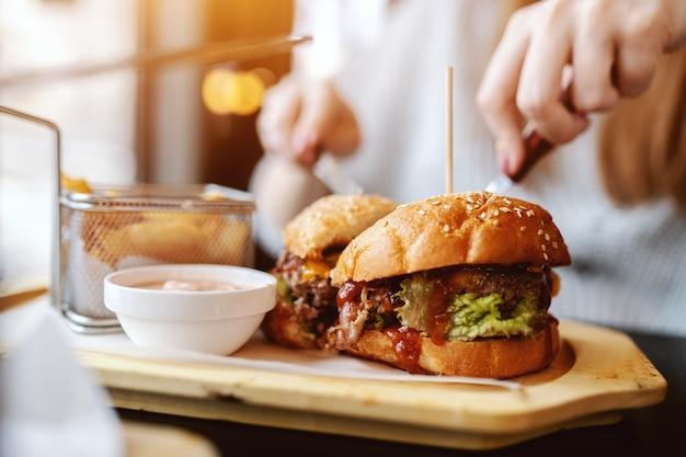 Gros plan d'une femme caucasienne, manger un délicieux hamburger alors qu'il était assis dans le restaurant.
