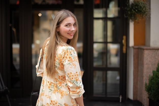 Gros plan d'une femme caucasienne souriante blonde dans une robe qui regarde par-dessus son épaule sur un fond de verre noir dans la ville