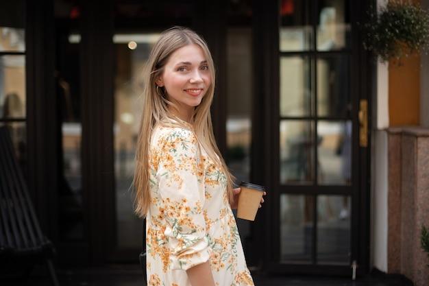 Gros plan d'une femme caucasienne souriante dans une robe buvant du café à emporter sur un fond de verre noir