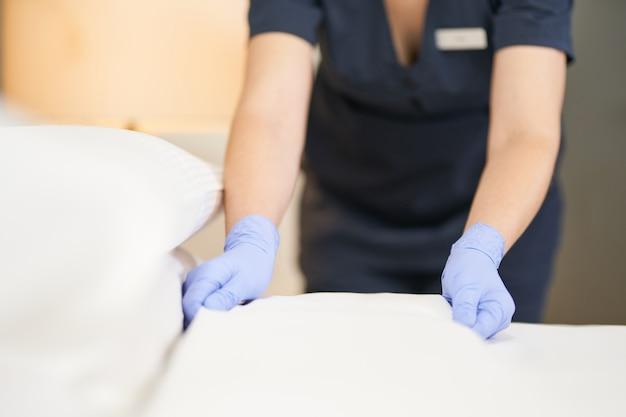 Gros plan d'une femme de chambre dans des gants de protection faisant un lit dans une chambre d'hôtel. concept de service hôtelier