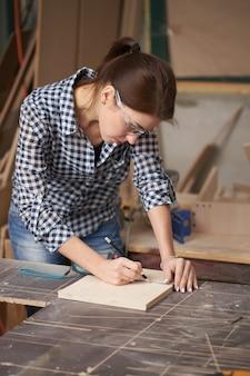 Gros plan sur une femme charpentière dans des verres avec un ruban à mesurer et un tableau noir en atelier