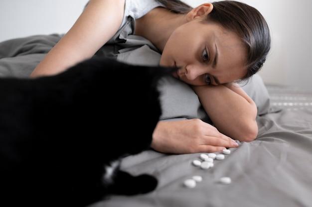 Gros plan femme avec chat et pilules