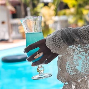Gros plan d'une femme en chemisier en dentelle tenant un verre avec un cocktail bleu