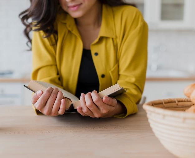 Gros plan femme avec chemisier jaune et livre