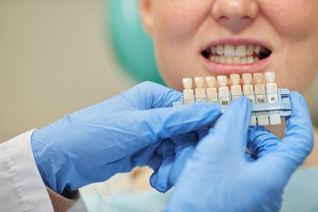 Gros plan d'une femme choisissant les implants lors de sa visite au bureau du dentiste