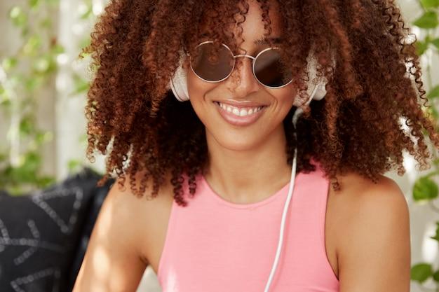 Gros plan d'une femme avec une coiffure afro touffue, une peau sombre et saine, passe du temps libre à écouter de la musique dans des écouteurs, apprécie la liste de lecture préférée, sourit joyeusement. femme meloman pose à l'intérieur