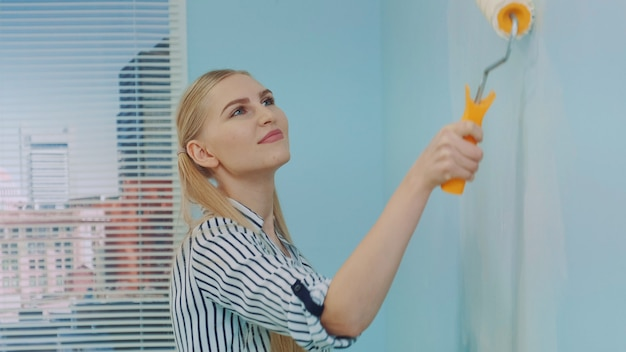 Gros plan de femme constructeur peinture mur.