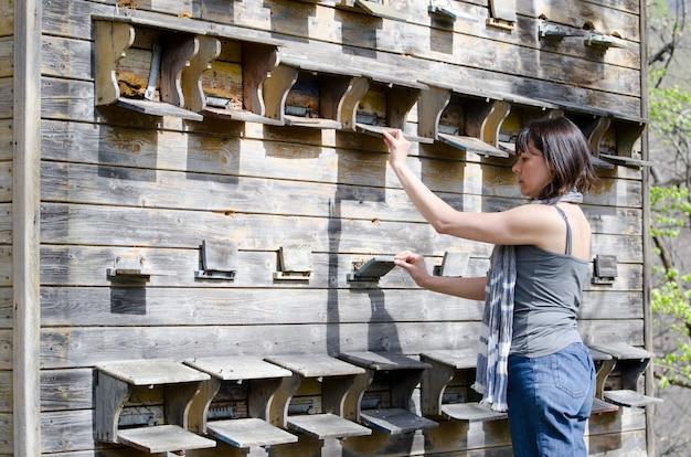 Gros plan d'une femme contrôlant sa maison d'apiculture