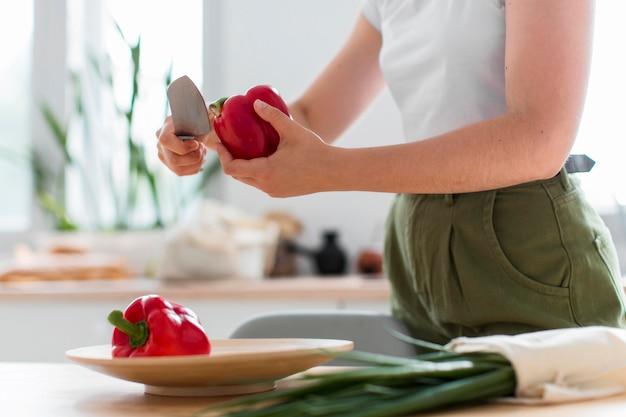 Gros plan, femme, couper, poivrons rouges bio