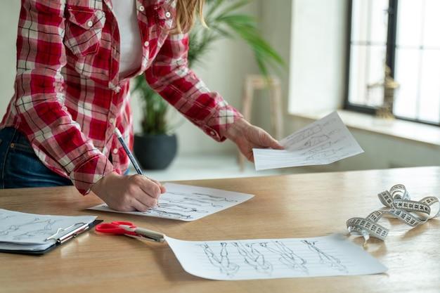 Gros plan femme créateur de mode main travaillant dans l'atelier de bureau fashionista élégante femme créant une nouvelle collection de conception de tissu couture et couture des gens mode de vie et de l'occupation