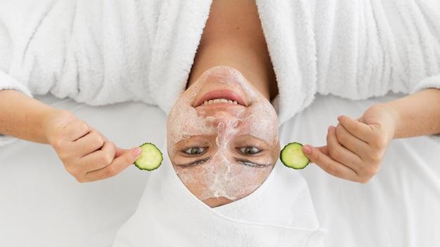 Gros plan femme avec crème pour le visage et concombres