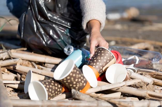 Gros plan, femme, cueillette, poubelle, bord mer