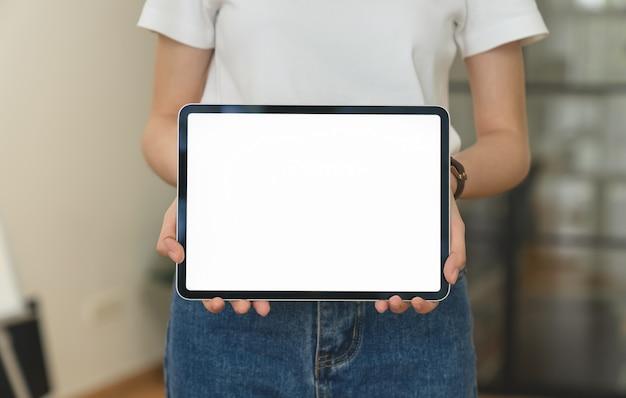 Gros plan de femme debout et main tenant une tablette numérique avec écran est vide sur le bureau.