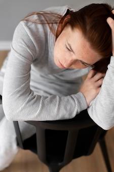 Gros plan femme déprimée assise sur une chaise