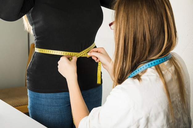 Gros plan, femme, diététicienne, mesurer, ventre patient, clinique