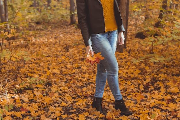 Gros plan sur une femme donne un coup de pied aux feuilles jaunes en automne. humeur triste et concept de trouble affectif saisonnier.