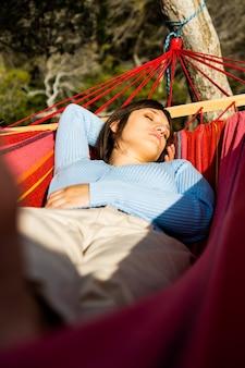 Gros plan d'une femme dormant dans un hamac en train de bronzer, photo verticale