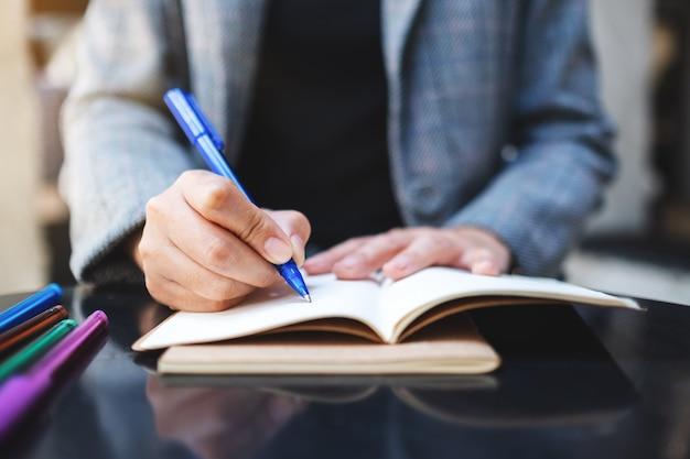 Gros plan d'une femme écrivant sur un cahier vierge avec des stylos de couleur sur la table