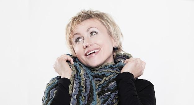 Gros plan .une femme élégante enveloppée dans une écharpe tricotée.isolé sur fond blanc.
