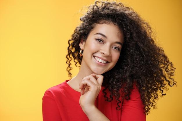 Gros plan d'une femme élégante et heureuse aux cheveux bouclés brillants en robe rouge, inclinant la tête, touchant sensuellement le menton avec le doigt et souriant largement, faisant un flirt regardant la caméra sur fond jaune.