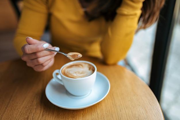 Gros plan d'une femme élégante tenant une cuillère pour brasser le café chaud.