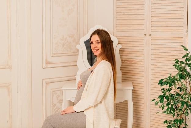 Gros plan d'une femme enceinte souriante heureuse touchant son ventre sur fond d'arbre de noël