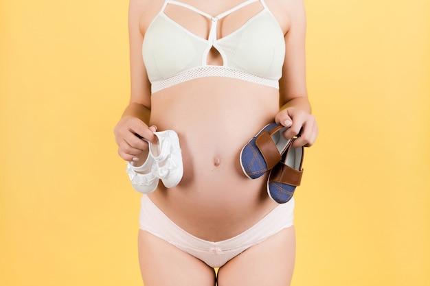 Gros plan d'une femme enceinte en sous-vêtements colorés tenant des chaussures de bébé pour un garçon et une fille contre son ventre à la surface jaune. copiez l'espace.