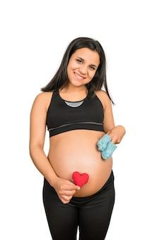 Gros plan d'une femme enceinte tenant des chaussettes pour bébé et signe de coeur sur le ventre. concept de grossesse, de maternité et d'attente.