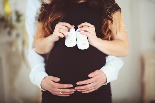 Gros plan d'une femme enceinte tenant des chaussures de bébé et de son mari à la maison