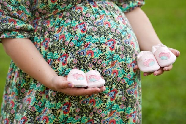 Gros plan d'une femme enceinte tenant des chaussures de bébé sur son ventre. jumeaux