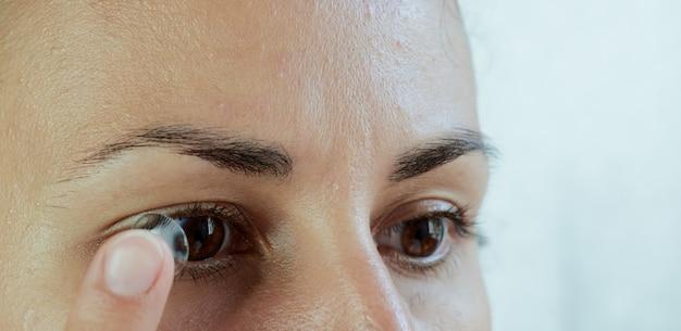 Gros plan d'une femme enlevant les lentilles de contact souples de son œil sur un fond blanc.