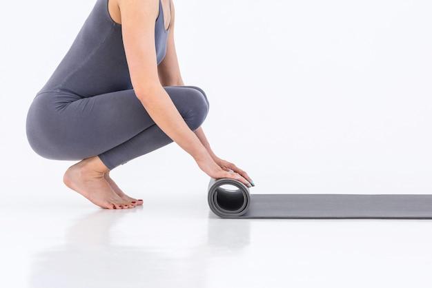 Gros plan femme enroule le tapis de yoga sur fond blanc. des exercices d'étirement