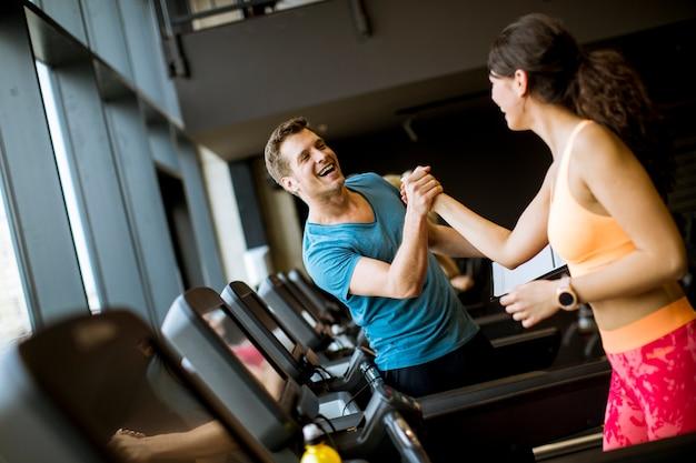 Gros plan de femme avec entraîneur travailler sur tapis roulant en salle de gym