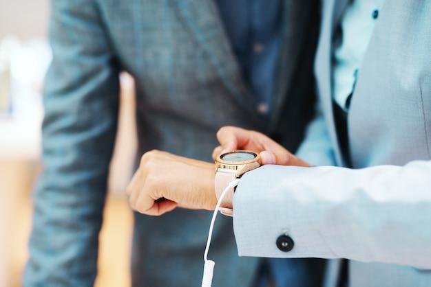 Gros plan de femme essayant une nouvelle montre-bracelet en se tenant debout dans le magasin tech.