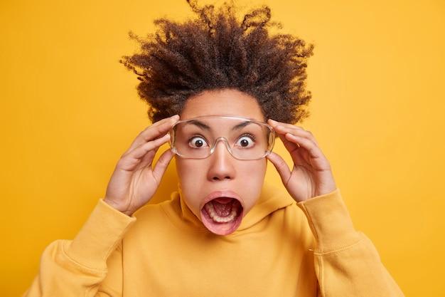 Gros plan d'une femme ethnique super choquée qui saute les yeux, garde la bouche grande ouverte remarque une scène terrible porte un sweat-shirt a les cheveux debout