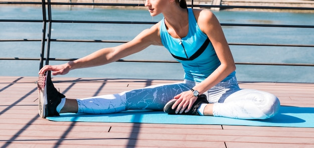 Gros plan, femme, étirement, main, jambe, séance, natte exercice