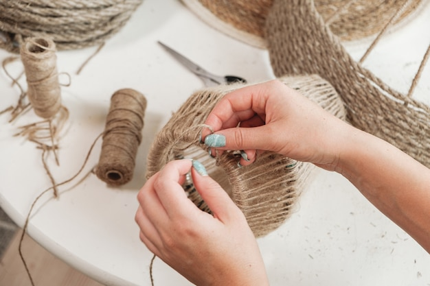 Gros plan femme fabrique une lampe de bricolage à la main à partir de corde de jute