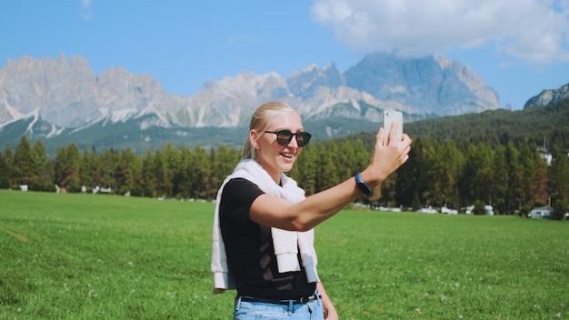 Gros plan d'une femme faisant un appel vidéo du magnifique parc naturel en face des montagnes. elle partage les impressions de son voyage.