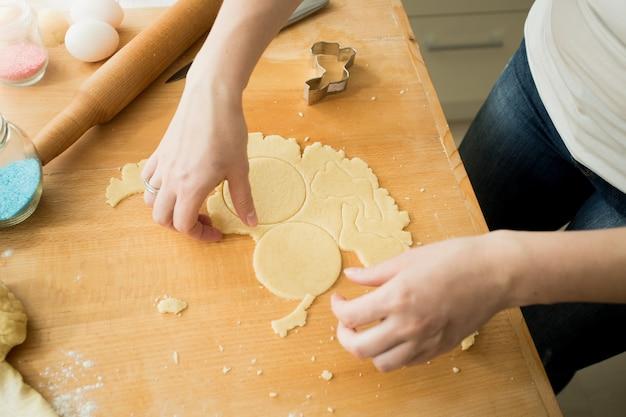 Gros plan d'une femme faisant des biscuits coupant la pâte avec du moule