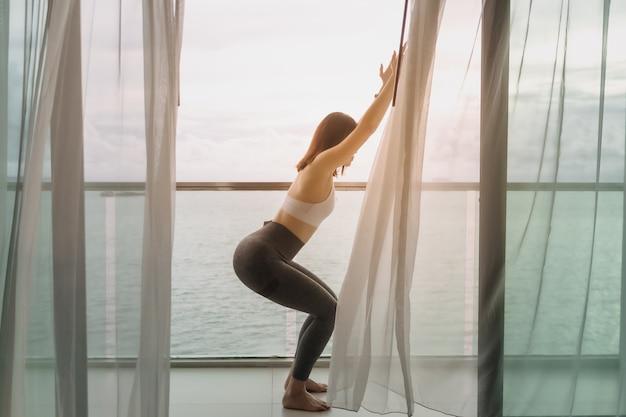 Gros plan d'une femme faisant une pose de yoga sur le balcon avec vue sur la mer